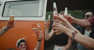 Party time in the middle of field group of 90 s friends cheers with the bottles of beer , stylish and happy faces. 4k. Party time in the middle of field group of stock footage