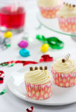 Party Time with tasty cream cupcakes and candy. Ideal party background with cream cupcakes, candy, soda pop and confetti streamers Royalty Free Stock Image