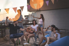 Party time. Young friends having fun at a rooftop party, playing the guitar, singing, dancing and chilling out. Focus on the girl playing the guitar Royalty Free Stock Photo