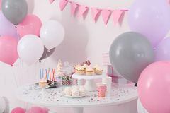 Party treats and items on table in room decorated. With balloons stock photo