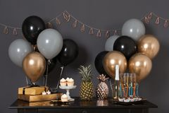 Party treats and items on table. In room decorated with balloons royalty free stock images