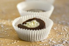 Party unbaked coffee anad coconut cookies in paper cupcakes on wooden bamboo table, shredded coconut. Delicious sweets Stock Photo