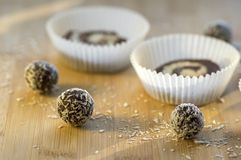Party unbaked coffee anad coconut cookies in paper cupcakes on wooden bamboo table, shredded coconut. Tasty balls Stock Images
