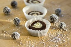 Party unbaked coffee anad coconut cookies in paper cupcakes on wooden bamboo table, shredded coconut, tasty balls. Delicious sweets Stock Image