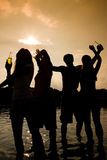 Party in the water. People (two couples) on the beach dancing to music, drinking and having a lot of fun in the sunset - only silhouette of people to be seen Royalty Free Stock Photography