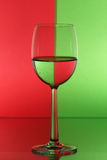 Party wine glass. Wine glass with red green background Stock Images