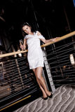 Party Woman. A glamorous young woman standing near a railing drinking champagne, at a party Stock Image