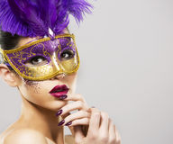 Party woman swearing golden mask on light backgound Royalty Free Stock Image