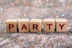 Party word. Wood Cubes Party word on glitter background royalty free stock photo