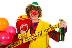 Party zone. Couple funny clowns with bottle wine in the party zone Royalty Free Stock Image