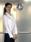 Partying Businesswoman. A businesswoman standing near a silver disco ball royalty free stock photography