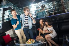 Partying friends. Excited friends having a karaoke party knocking themselves out Royalty Free Stock Photo