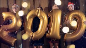 Partying friends hold balloons in shape of number 2019. Happy new year concept. New Year party goers hugging large balloons making a number 2019 stock video footage