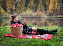 Partying. Haughty woman with a basket of apples on a picnic royalty free stock photography