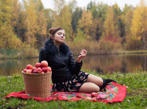 Partying. Haughty woman with a basket of apples on a picnic stock photo