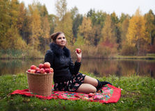 Partying. Haughty woman with a basket of apples on a picnic royalty free stock image
