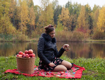Partying. Haughty woman with a basket of apples on a picnic royalty free stock photo