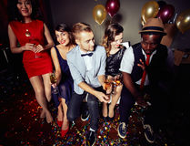 Partying at Night Club. High angle view of multi-ethic group of friends partying at trendy night club and celebrating New Years Eve, full-length portrait royalty free stock photo