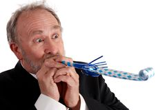 Partying senior business man. Senior businessman blowing a noisemaker wearing a suit Royalty Free Stock Images