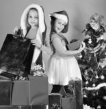 Partying and xmas sale concept. Sisters in Santa Claus hats. With gift boxes open presents. Girls celebrate New Year. Children with happy faces enjoy presents stock photo