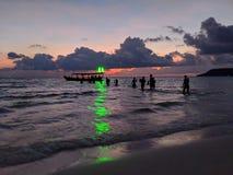 Partyjny tłum watuje z powrotem łódź w kierunku zielonego światła od plaży w Koh Rong, Kambodża zdjęcie stock