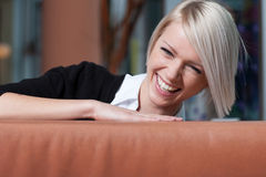 Partytime. Laughing vivacius woman with short blonde hair and a merry smile looking over the top of a sofa conceptual of celebrating and partytime Stock Image