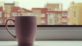 Parująca gorąca filiżanka herbaciana pozycja na okno w Śnieżnym zima ranku Wygodny Różowy kawowy kubek Opad śniegu z wielkimi pła zbiory wideo