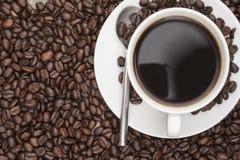 Parująca gorąca filiżanka kawy i fasole Obrazy Stock