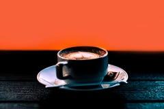 Parującej kawowej Latte sztuki Kierowa filiżanka na zmroku z Pomarańczowym backgrou Zdjęcia Royalty Free