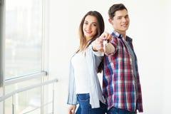 Parvisningtangenter till nytt hem- krama som packar upp tillsammans kortet royaltyfria bilder