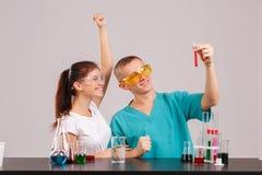 Pary asystenci cieszą się pomyślnego eksperyment z czerwonym cieczem, trzyma kolbę zdjęcia royalty free