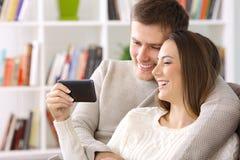 Pary dopatrywanie na linii zawartości w mądrze telefonie w domu obrazy royalty free