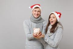 Pary dziewczyny facet w czerwonym Santa pulowerów scarves chwyta Bożenarodzeniowym kapeluszowym szarym prosiątku odizolowywającym zdjęcia stock