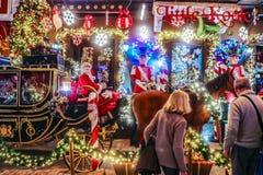 Pary fermata podziwiać Bożenarodzeniowe dekoracje przy Małym Kook - bajki sprzedawania o temacie cukierniani cukierki fotografia stock