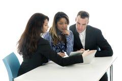 Pary i biznesowej kobiety spojrzenie przy laptopu obsiadaniem przy stołem zdjęcia stock