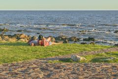 Pary lying on the beach przy nabrzeże parkiem, Montevideo, Urugwaj obrazy stock