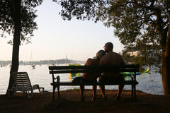 Pary obsiadanie na ławce przy zmierzchem Zdjęcia Royalty Free