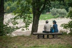 Pary obsiadanie na ławce w rabatowym jeziorze Fotografia Stock