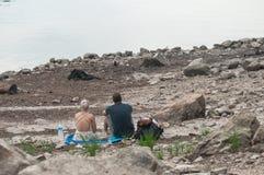 Pary obsiadanie na kamieniu w rabatowym jeziorze Obrazy Stock