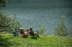 Pary obsiadanie na krzesłach w rabatowym jeziorze Zdjęcie Royalty Free