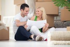 Pary obsiadanie na podłogowych patrzeje domowych planach Zdjęcia Stock