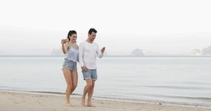 Pary odprowadzenie Na Plażowych Używa komórka Mądrze telefonach Bierze Selfie mienia ręki, młody człowiek kobiety turystów networ zbiory