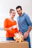 Pary oszczędzania pieniądze ruszać się dom Zdjęcia Stock