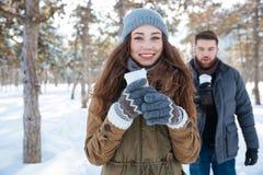 Pary pozycja z kawą w zima parku Fotografia Royalty Free