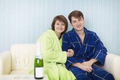 pary szczęśliwy kanapy lśnienia wino Zdjęcia Stock