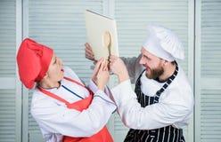 Pary walka dla książkowych przepisów r Ksi??kowi przepisy Pomocniczo kulinarna ksi??ka Kobieta m??czyzny i szefa kuchni kucharstw obrazy royalty free