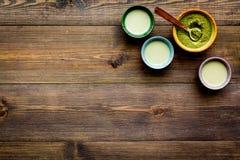 Parzenia matcha herbata Rzuca kulą z proszkiem i filiżankami z napojem na ciemnej drewnianej tło odgórnego widoku kopii przestrze Zdjęcie Stock