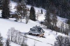 País nevoso escarchado con las casas en un día de invierno soleado Imágenes de archivo libres de regalías