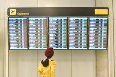 Pasażerski sprawdza lota status przy lotniskowym ewidencyjnym pokazem zdjęcie stock