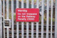 Pasażerski znak ostrzegawczy przy kolejowym dworcem twierdzi no naruszenie własności lub kara grzywna wyd jeżeli ty krzyżujesz sz zdjęcia stock